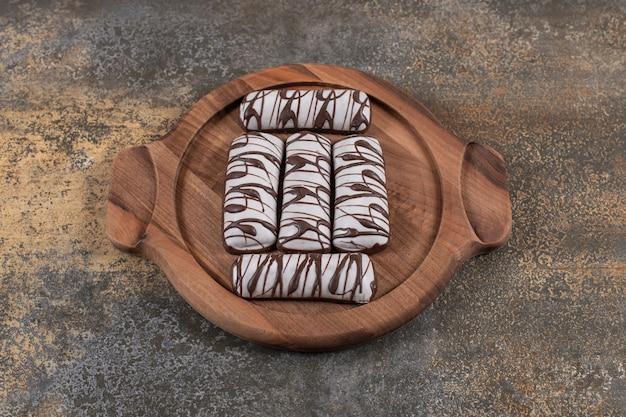 Bovenaanzicht van verse platte taarten op houten dienblad.