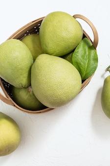 Bovenaanzicht van verse pomelo in een mand met vruchtvlees