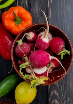 Bovenaanzicht van verse radijs in een houten kom en verse kleurrijke paprika komkommers en citroen op donker hout