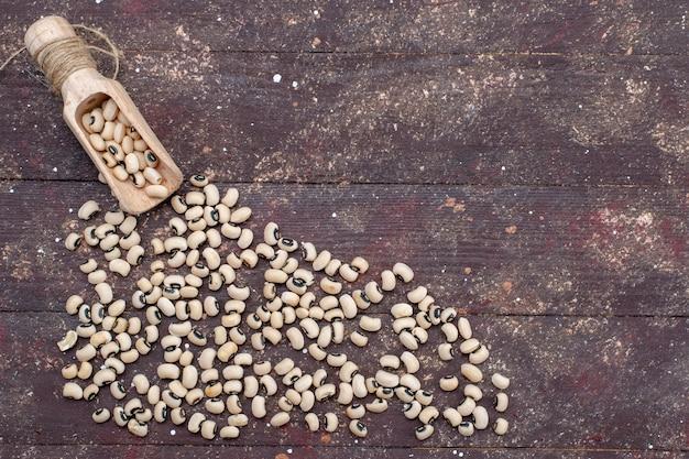 Bovenaanzicht van verse rauwe bonen verspreid over de bruine, rauwe bonen snijbiet