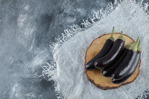 Bovenaanzicht van verse rauwe paarse aubergines op een houten bord.
