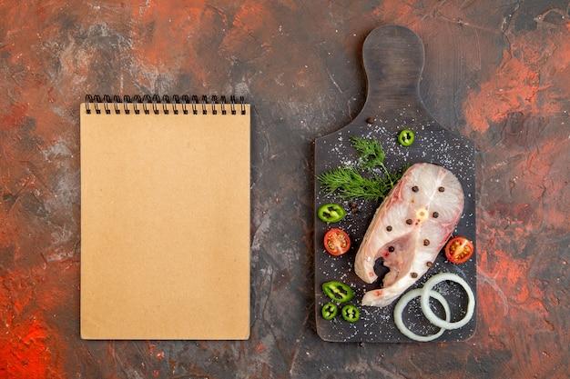 Bovenaanzicht van verse rauwe vissen en peper-ui groenen tomaten op zwarte snijplank notebook op gemengde kleur oppervlak