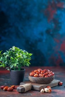 Bovenaanzicht van verse rauwe zilverbessenvruchten in een houten kom op een snijplank en bloempot op een achtergrond van mixkleuren