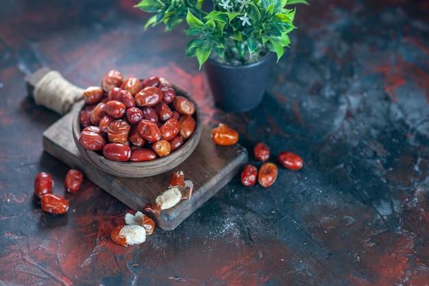 Bovenaanzicht van verse rauwe zilverbessenvruchten in een kom op een houten snijplank en bloempot aan de rechterkant op de achtergrond van mixkleuren