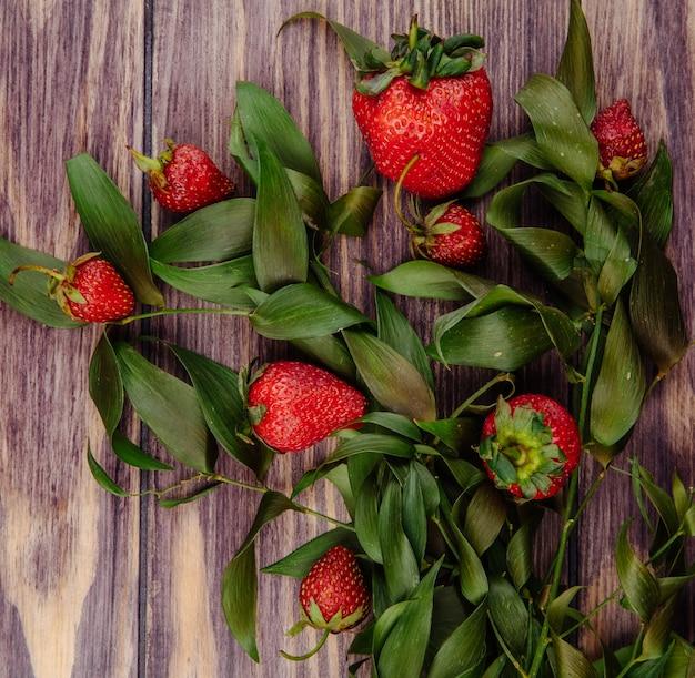 Bovenaanzicht van verse rijpe aardbeien en groene bladeren op hout