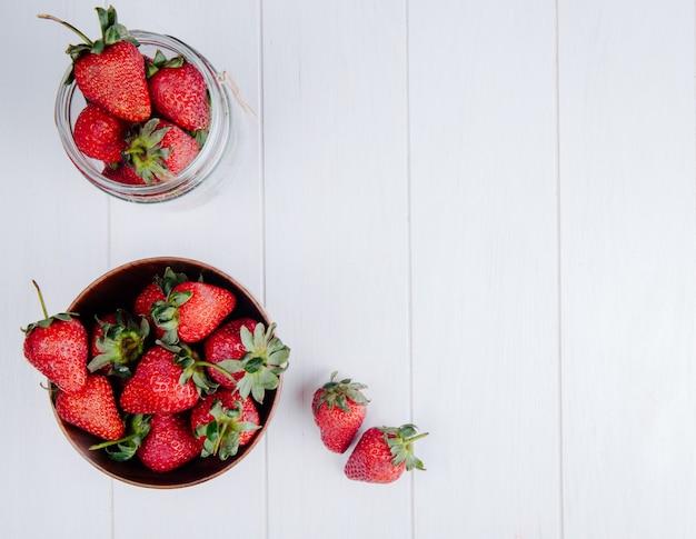 Bovenaanzicht van verse rijpe aardbeien in een houten kom op wit met een kopie ruimte