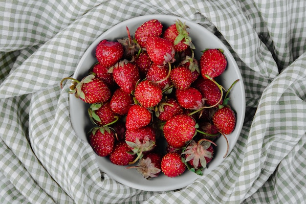 Bovenaanzicht van verse rijpe aardbeien in een kom op geruite stof