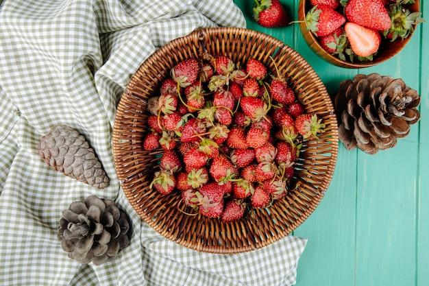 Bovenaanzicht van verse rijpe aardbeien in een rieten mand en kegels op groen hout
