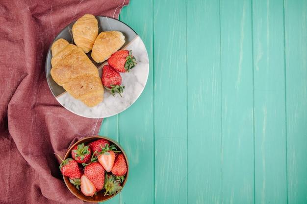 Bovenaanzicht van verse rijpe aardbeien met croissants op een plaat op groen hout met kopie ruimte