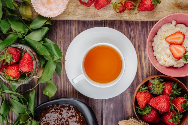 Bovenaanzicht van verse rijpe aardbeien met jam kwark en een kopje thee op rustieke houten tafel
