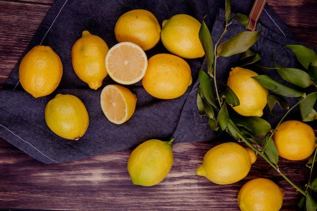 Bovenaanzicht van verse rijpe citroenen op zwarte stof op rustieke