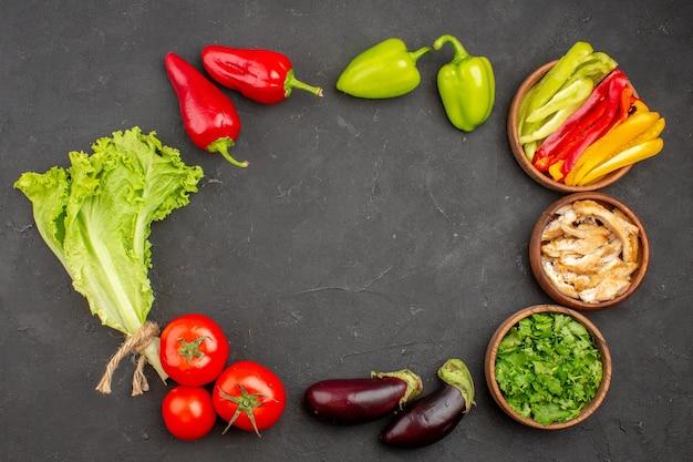 Bovenaanzicht van verse rijpe groenten met groenen op zwart