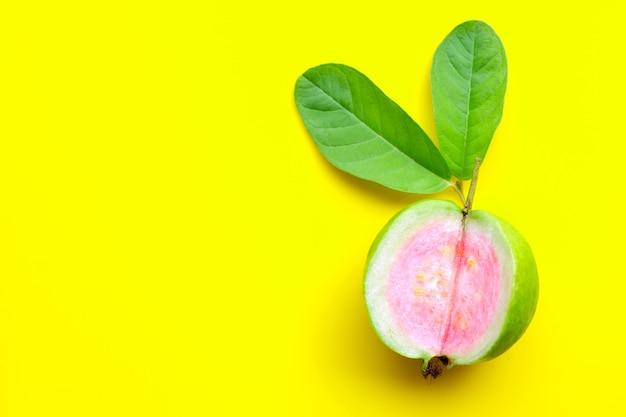 Bovenaanzicht van verse rijpe guave met blad op gele achtergrond.