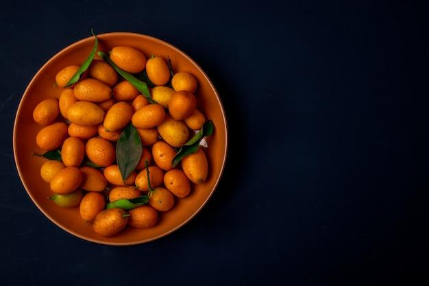 Bovenaanzicht van verse rijpe kumquats op een bord op zwart oppervlak met kopie ruimte