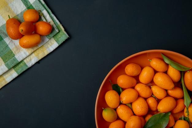 Bovenaanzicht van verse rijpe kumquatvruchten op een plaat op zwarte met exemplaarruimte