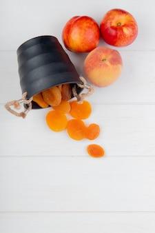 Bovenaanzicht van verse rijpe nectarines en gedroogde abrikozen verspreid uit kleine emmer op wit