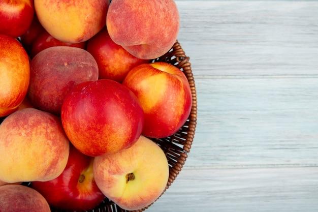 Bovenaanzicht van verse rijpe nectarines en perziken in een rieten mand op witte achtergrond met kopie ruimte
