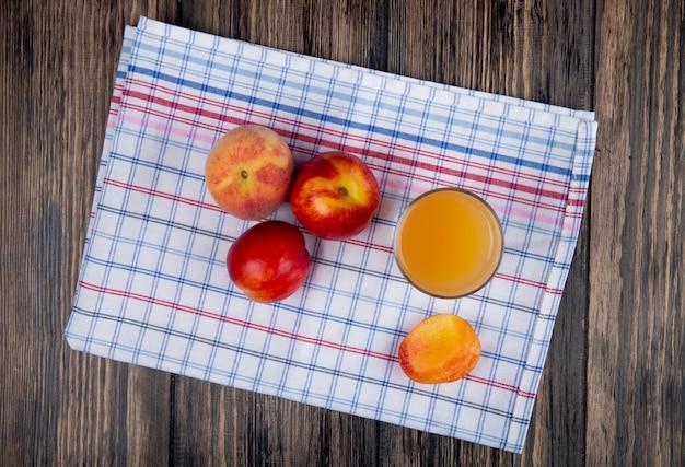 Bovenaanzicht van verse rijpe nectarines en perziken met een glas perziksap op plaidservet op rustiek hout