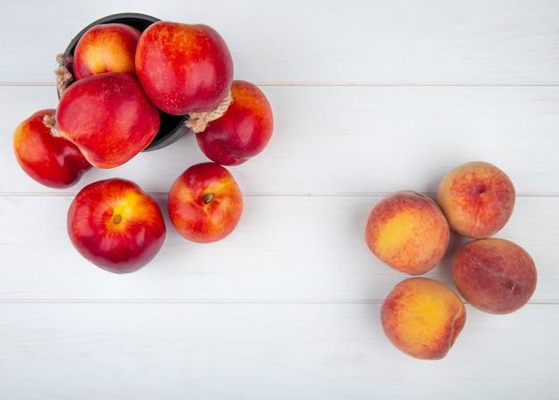 Bovenaanzicht van verse rijpe nectarines in een kleine emmer en verse perziken op wit