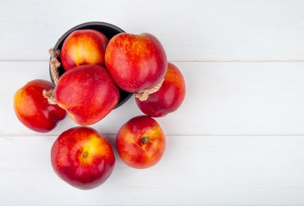 Bovenaanzicht van verse rijpe nectarines in een kleine emmer op wit met een kopie ruimte