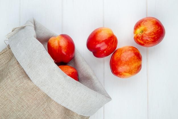 Bovenaanzicht van verse rijpe nectarines verspreid uit een zak op wit