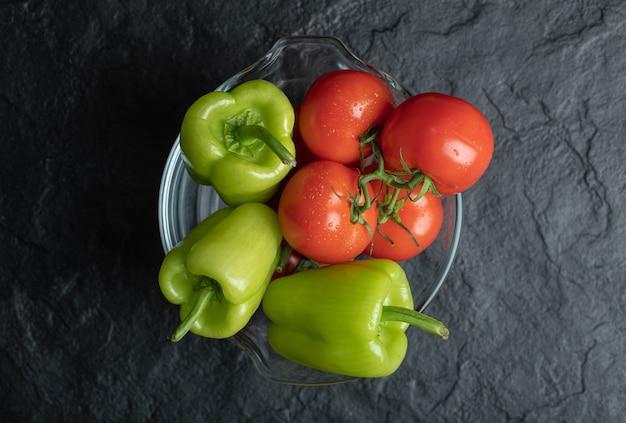 Bovenaanzicht van verse rijpe paprika's en tomaten in glazen kom op zwarte achtergrond