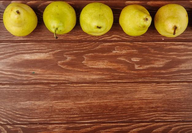 Bovenaanzicht van verse rijpe peren in een lijn op een houten achtergrond met kopie ruimte