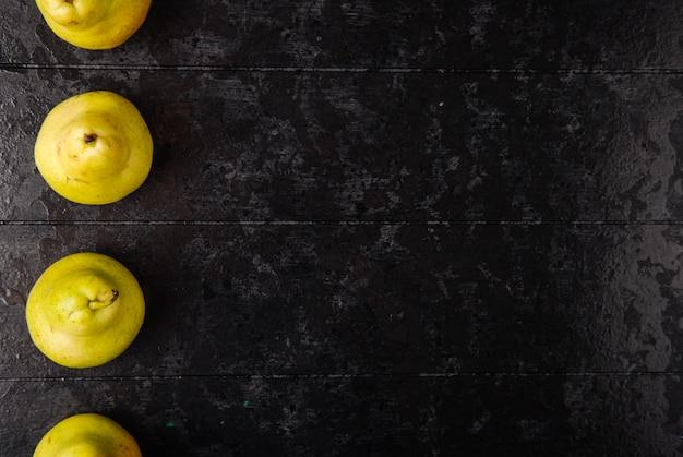 Bovenaanzicht van verse rijpe peren in een lijn op zwarte houten achtergrond met kopie ruimte