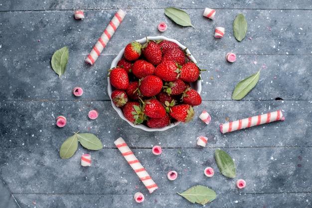 Bovenaanzicht van verse rode aardbeien in plaat samen met stoksnoepjes en groene bladeren op grijs, fruit bessen vers snoepje zoet