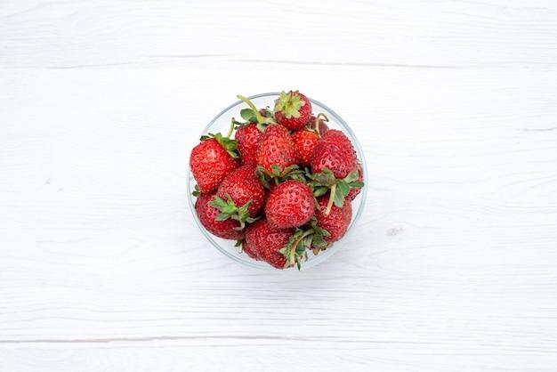 Bovenaanzicht van verse rode aardbeien in transparante plaat op licht wit, vers fruit