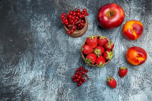 Bovenaanzicht van verse rode aardbeien met perziken en appel op donkere ondergrond