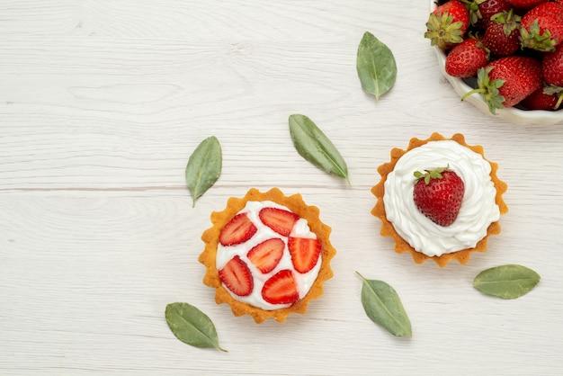Bovenaanzicht van verse rode aardbeien zachte en heerlijke bessen in witte plaat met gebak op licht, fruit berry rood