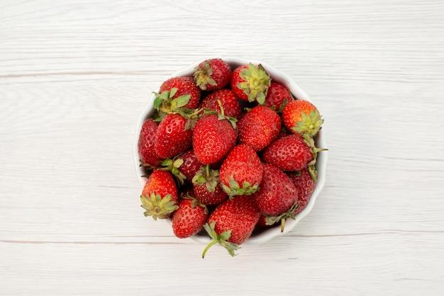 Bovenaanzicht van verse rode aardbeien, zachte en heerlijke bessen in witte plaat op licht, fruit bessen verse rode kleur