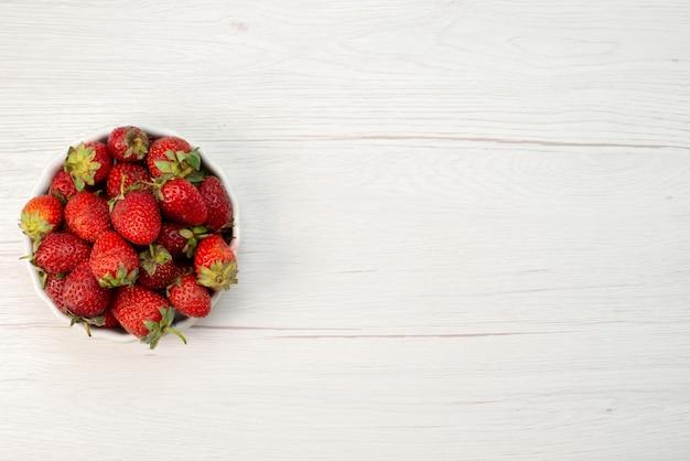 Bovenaanzicht van verse rode aardbeien, zachte en heerlijke bessen in witte plaat op licht, fruit bessen verse rode kleurenfoto