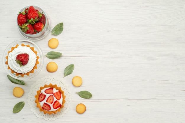 Bovenaanzicht van verse rode aardbeien zachte en heerlijke bessen met taarten en koekjes op licht bureau, fruit bessen rood vers