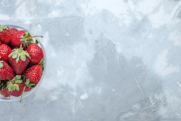 Bovenaanzicht van verse rode aardbeien, zachte zomerbessen in glazen plaat op licht bureau