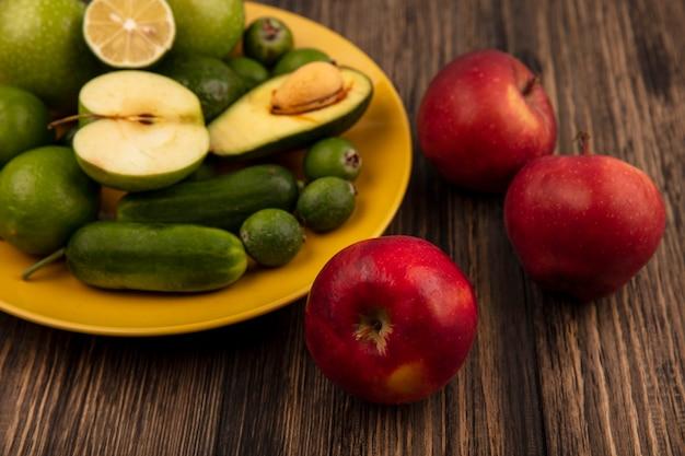 Bovenaanzicht van verse rode appels met vers fruit zoals groene appels limoenen feijoas en avocado's op een gele plaat op een houten muur