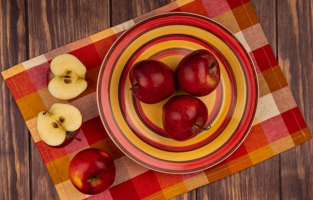 Bovenaanzicht van verse rode appels op een plaat op een gecontroleerde doek met gehalveerde appels geïsoleerd op een houten muur