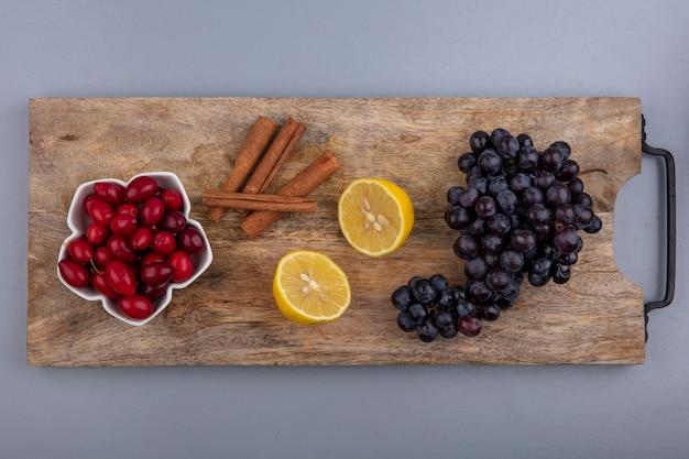 Bovenaanzicht van verse rode cornel bessen op een kom met citroen-kaneelstokjes en druiven op een houten keukenbord op een grijze achtergrond