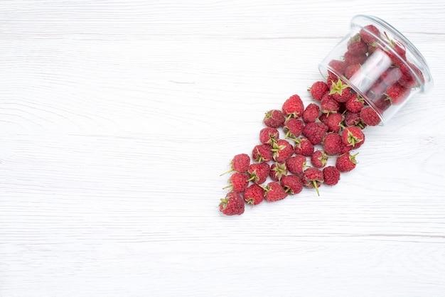 Bovenaanzicht van verse rode frambozen binnen en buiten plaat op licht-wit, vers fruit