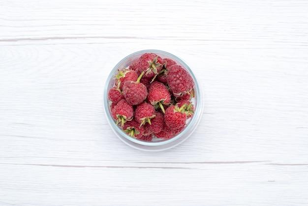 Bovenaanzicht van verse rode frambozen in transparante kom op wit, vers fruit