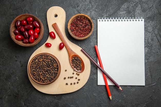 Bovenaanzicht van verse rode kornoeljes met kruiden op donkergrijs oppervlak