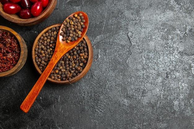 Bovenaanzicht van verse rode kornoeljes met kruiden op grijze ondergrond
