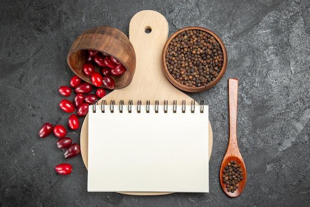 Bovenaanzicht van verse rode kornoeljes met peper op het grijze oppervlak