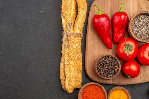 Bovenaanzicht van verse rode tomaten met brood en kruiden op zwart