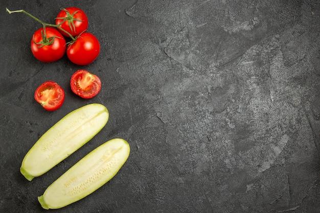 Bovenaanzicht van verse rode tomaten met pompoenen op grijze ondergrond