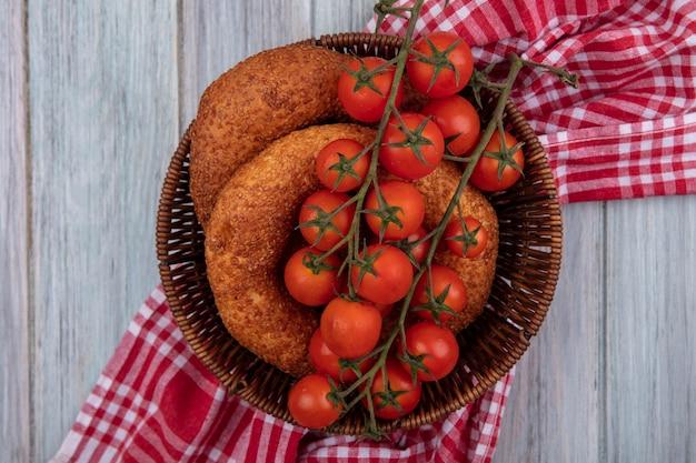 Bovenaanzicht van verse rode tomaten op een emmer met bagels op een zakdoek op een grijze houten achtergrond