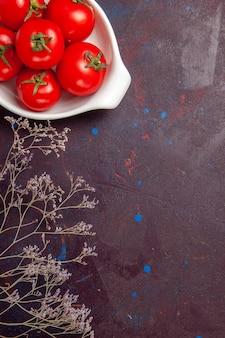 Bovenaanzicht van verse rode tomaten, rijpe groenten in plaat op zwart