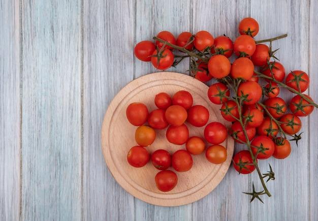 Bovenaanzicht van verse rode trostomaten op een kom met tomaten geïsoleerd op een houten keukenbord op een grijze houten achtergrond met kopie ruimte