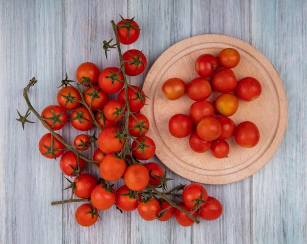 Bovenaanzicht van verse rode trostomaten op een kom met tomaten geïsoleerd op een houten keukenbord op een grijze houten achtergrond